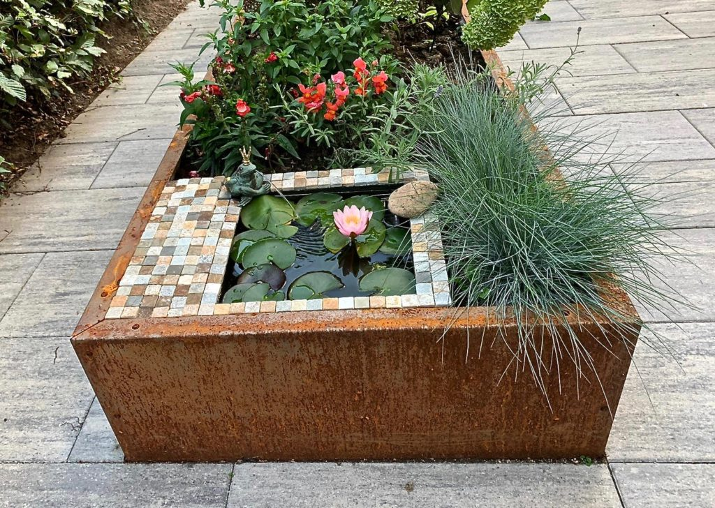 Kleiner Mosaikbrunnen in einem Hochbeet